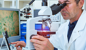 pathologist looking into microscope